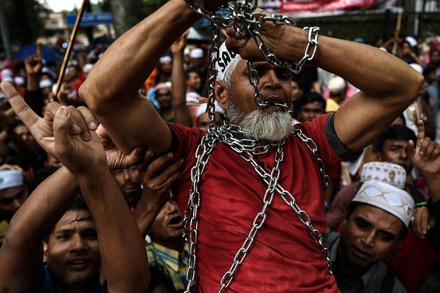 Ethnic Rohingya Muslim refugees shout slogans as they carry a man in chains during a protest against the persecution of Rohingya Muslims in Myanmar, outside the Myanmar Embassy in Kuala Lumpur on Nov 25, 2016.