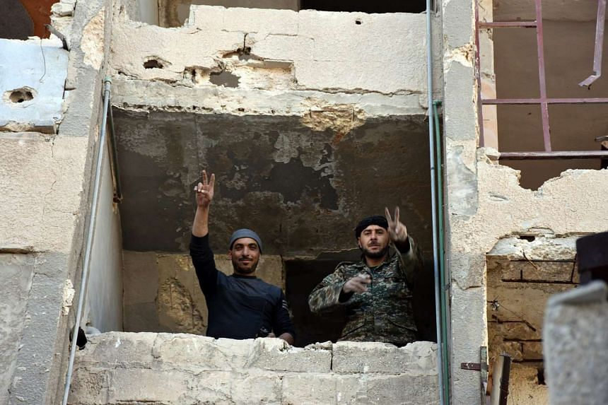 A handout picture made available by the official Syrian Arab News Agency shows Syrian soldiers making a V for victory sign from a window of damaged building in Aleppo's eastern Masaken Hanano area in Aleppo province on Nov 27, 2016.