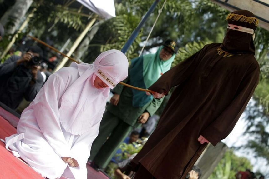 An Acehnese woman is whipped in front of the public by a punisher in Banda Aceh, Indonesia on Nov 28, 2016.