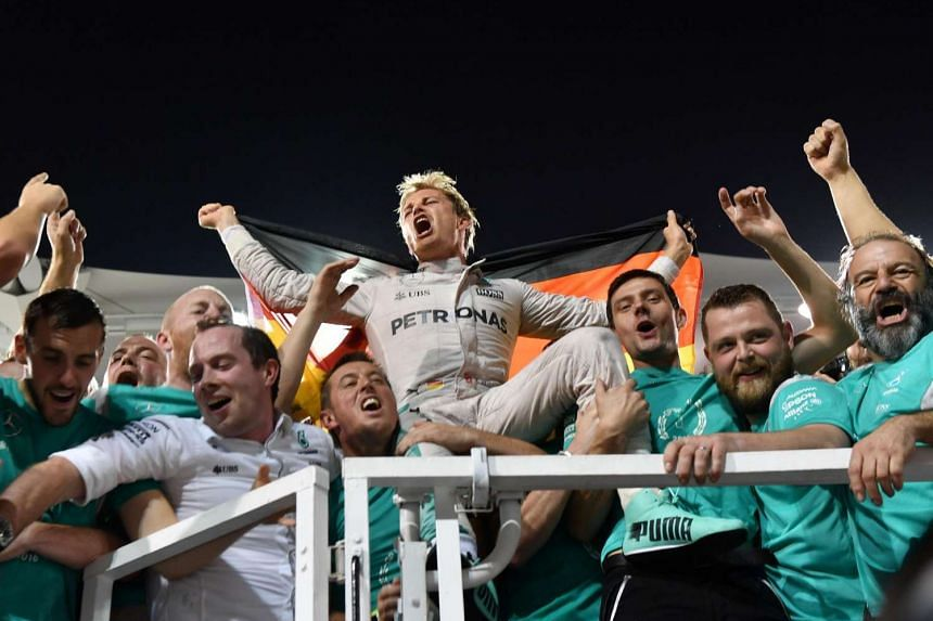 Mercedes AMG Petronas F1 Team's German driver Nico Rosberg celebrates with teammates at the end of the Abu Dhabi Formula One Grand Prix at the Yas Marina circuit on Nov 27, 2016.