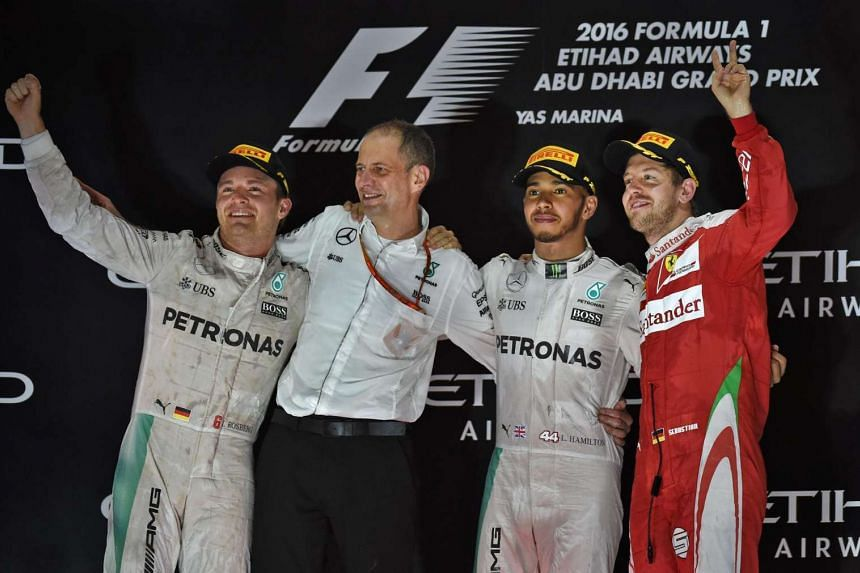 Mercedes AMG Petronas F1 Team's German driver Nico Rosberg, senior race engineer Tony Ross, British driver Lewis Hamilton and Scuderia Ferrari's German driver Sebastian Vettel celebrate on the podium at the end of the Abu Dhabi Formula One Grand Prix