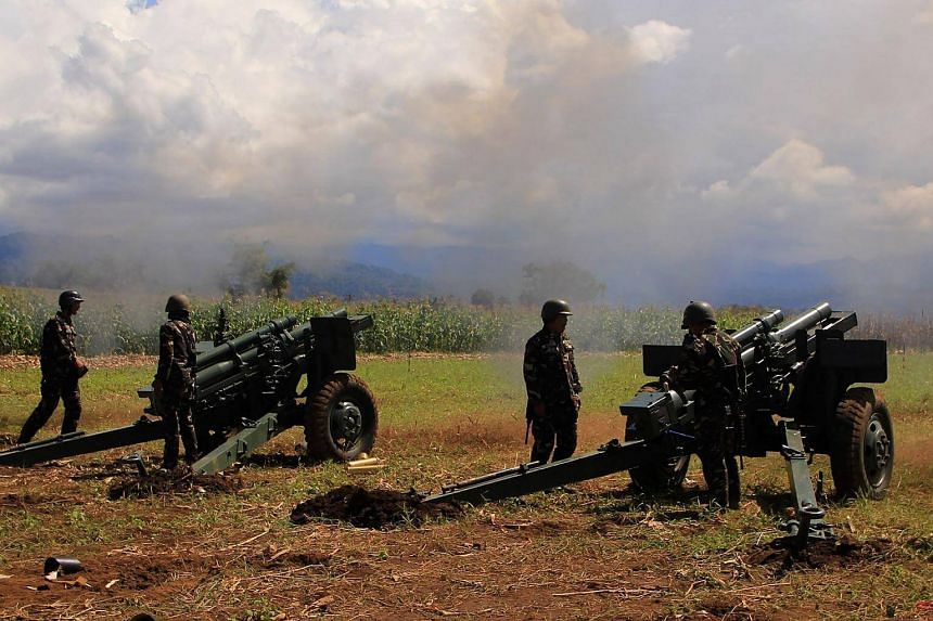 Philippine troops fire their 105mm howitzer cannons towards enemy positions from their base near Butig town in Lanao del Sur province on the southern island of Mindanao on Nov 27, 2016.