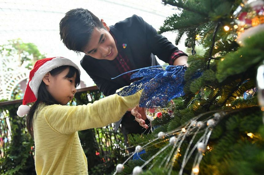 Nathan Hartono (right) helping Vania Ng, 6, hang her bauble on a Christmas tree in the Flower Dome at Gardens by the Bay on Nov 27 2016.