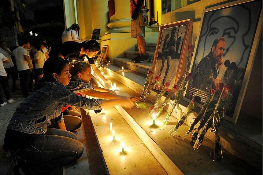 "Students lighting candles in honour of Dr Castro on Saturday at his alma mater Havana University, where hundreds gathered to wave Cuban flags and shout: ""Viva Fidel and Viva Raul."" A series of memorials will begin today, when Cubans will converge on"