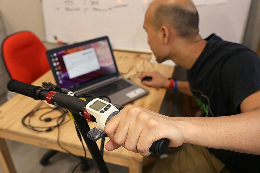 Mr Lee (left) of e-scooter retailer Falcon PEV (above) showing how the device's speed limit can be adjusted using a computer program. He estimates that there are 10,000 non-compliant e-scooters in Singapore.