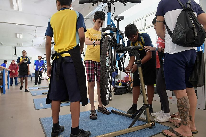 Crest Secondary School students demonstrating their bicycle repair skills to potential students and their parents. (From left) Nur Halif Abdullah Sani, Enrique Markus Monteiro and Ryan Ang have benefited from their practice- oriented education at Cre