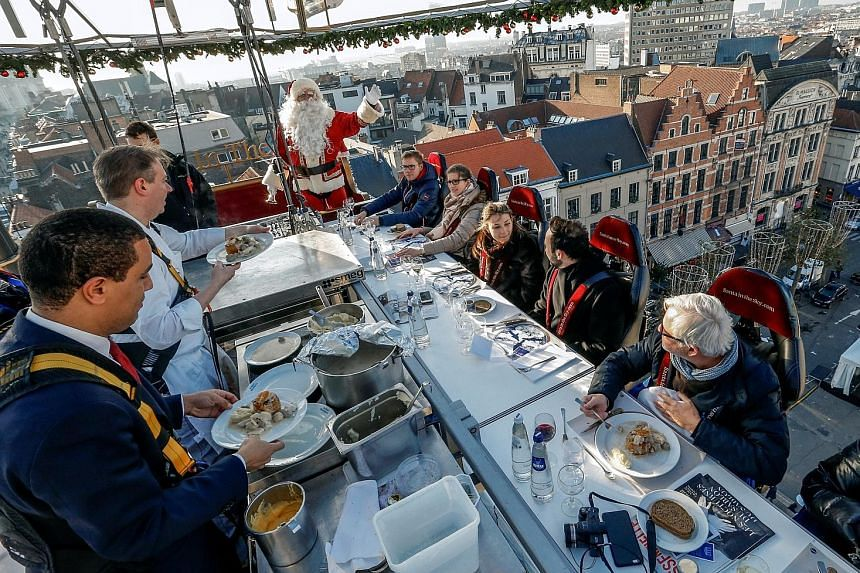 Chefs in safety harnesses serving diners strapped to chairs and suspended on an open platform 35m from the ground - during the Santa In The Sky event as part of Christmas festivities in Brussels on Friday.