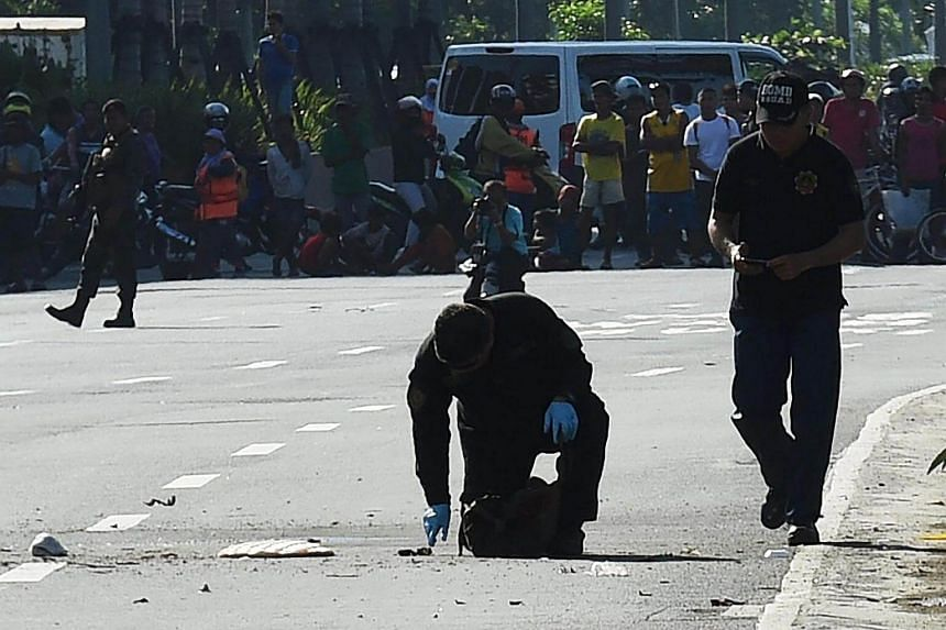 Members of the police bomb disposal unit inspect a suspicious package near the US Embassy in Manila on Nov 28, 2016.
