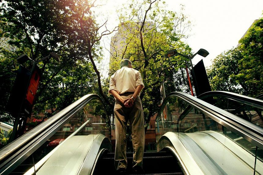 An elderly person going up the escalator. Old-timers at work typically have the wisdom to do the job better and more efficiently.