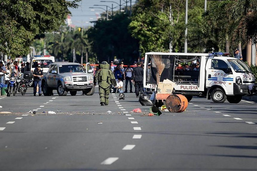A bomb squad operative wearing a suit walks off after inspecting a suspected improvised explosive device found near the US Embassy in Manila on Nov 28, 2016.