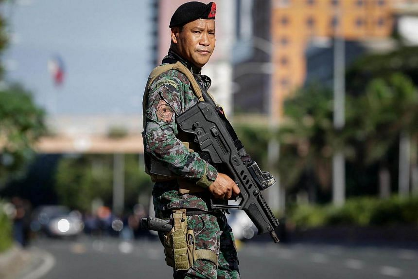 A member of the Philippine National Police Special Action Force patrols the area where a suspected improvised explosive device was found near the US Embassy in Manila on Nov 28, 2016.