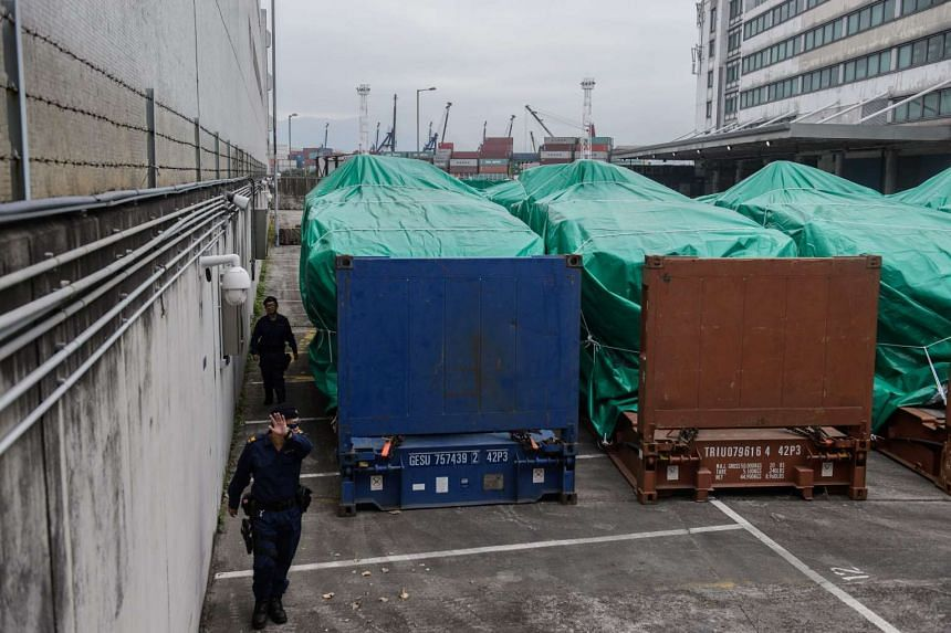 A member of security gestures near tarpaulin-covered armoured vehicles belonging to the Singapore military at a customs and excise facility in Hong Kong, on Nov 25, 2016.