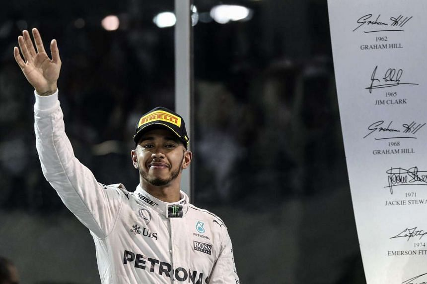 Formula One driver Lewis Hamilton of Mercedes AMG GP celebrates on the podium after his victory on the Abu Dhabi Formula One Grand Prix on Nov 27, 2016.
