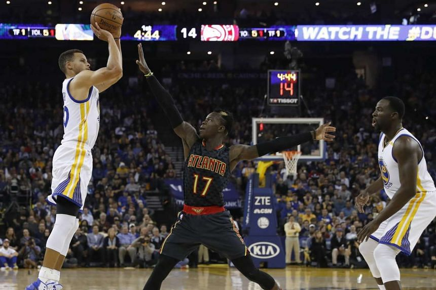 Golden State Warriors' guard Stephen Curry (left) shoots a jumper as Atlanta Hawks' guard Dennis Schroeder (center) defends during the first half of their NBA game at Oracle Arena in Oakland, California, on Nov 28, 2016.
