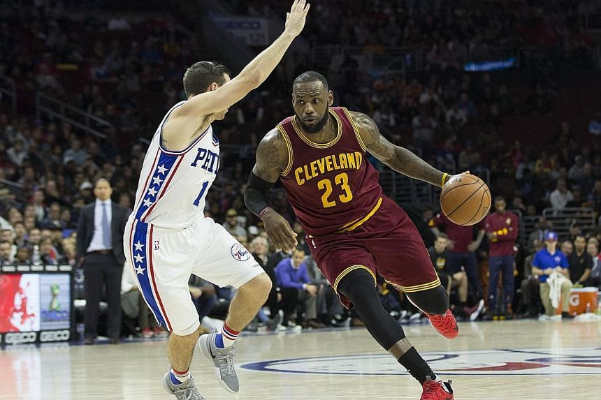 James driving to the basket against Sixers guard T.J. McConnell on Sunday. The Cavs beat the Sixers for the eighth straight time.