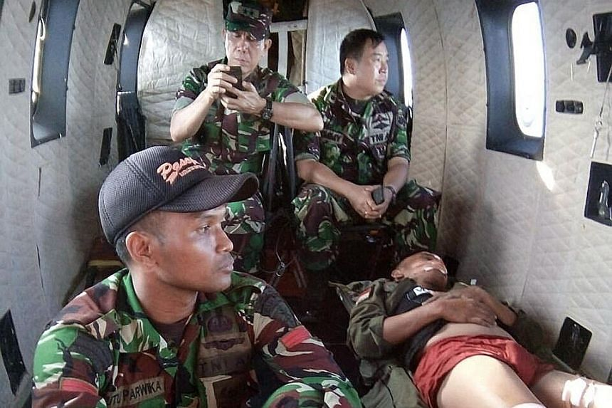 Indonesian helicopter pilot Abdi Damain being airlifted to safety on Sunday. However, four other crew members are still missing.