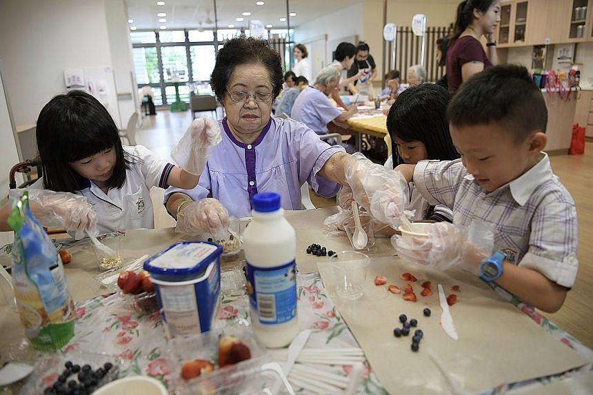 """Madam Oh Quee Eng, 80, making yogurt treats with children at Yishun Community Hospital. Health Minister Gan Kim Yong, who officially opened the hospital yesterday, said community hospitals can """"help patients improve their functions and regain confide"""