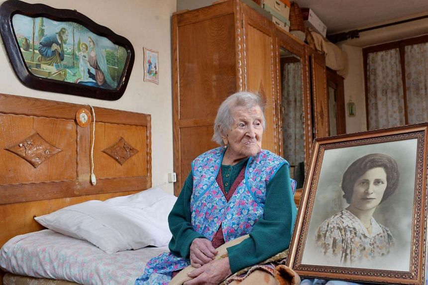 Italian Emma Morano sits next to a portrait of her in her younger days in her apartment in Verbania, northern Italy, on May 13, 2016.