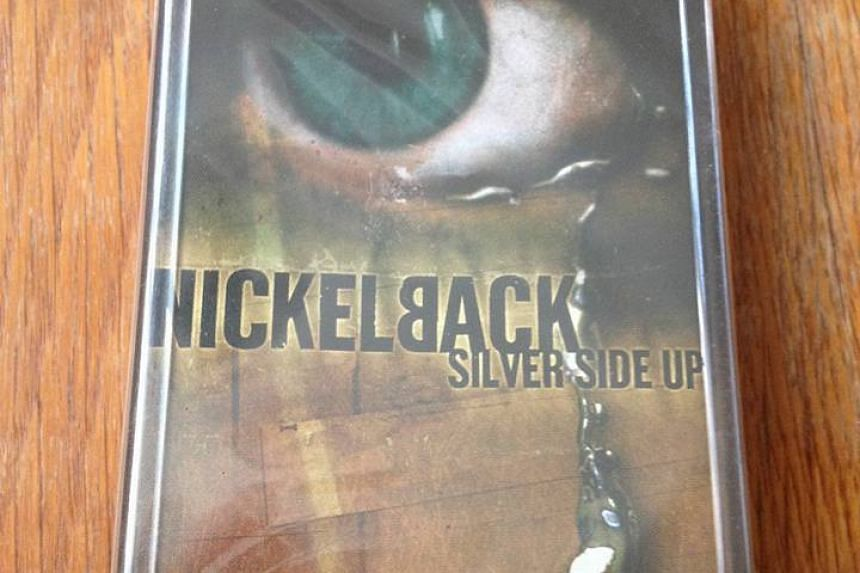 A cassette tape of Silver Side Up (2001) by Nickelback in its plastic wrapping.
