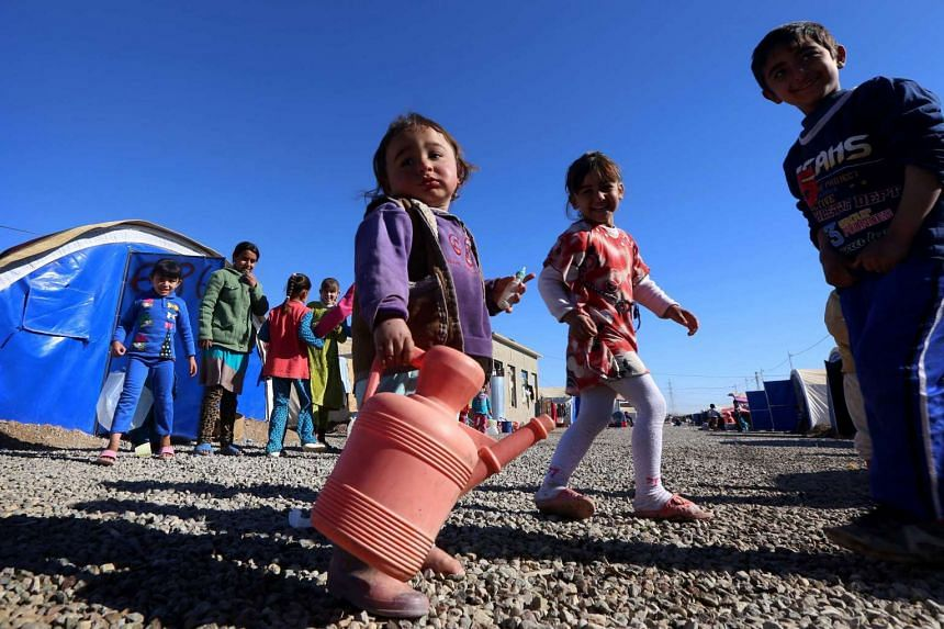 A displaced Iraqi girl in Mosul carries a jug of water at the al-Khazar camp on Nov 25, 2016