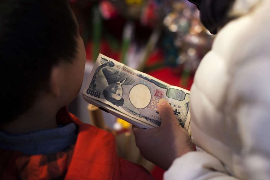 A customer holds a stack of 1,000 Japanese yen banknotes while making a purchase during the annual Tori-no-Ichi Fair at the Ohtori Shrine in Tokyo on Nov 25, 2016.