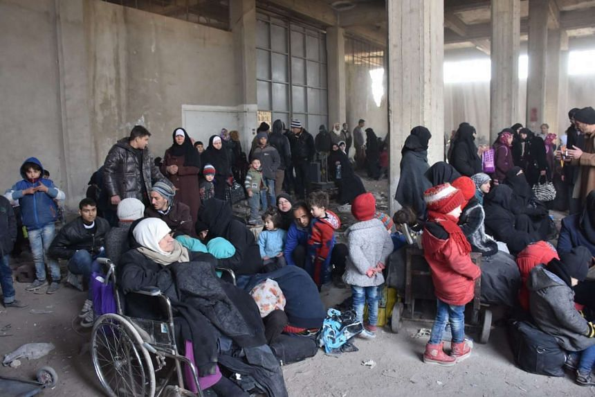 Displaced Syrian families evacuated from eastern neighbourhoods of Aleppo wait to ascend the buses at Baddour mount in Aleppo on Nov 29, 2016.