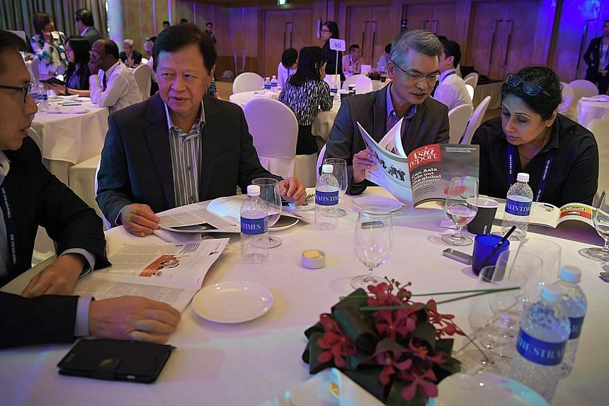 Participants at the ST Global Outlook Forum looking yesterday at the latest issue of the ST Asia report, a regular publication which compiles some of the best commentaries from its correspondents around the region. At the annual forum in the Ritz-Car