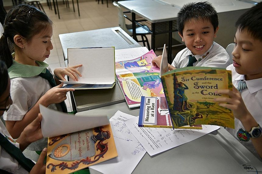 Primary 4 pupils (from left) Vasudevan Suresh Megna (partially hidden), Ellyse Wong, Tan Hai Yang and Bryan Pak with some of the storybooks used in their maths lessons at Woodgrove Primary School, which piloted the literature-based approach in 2014.