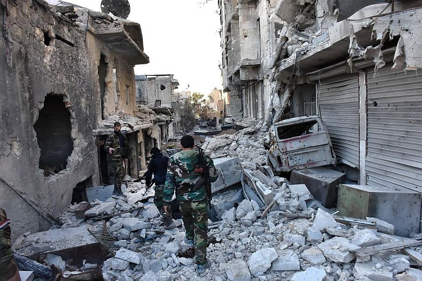 Syrian pro-government forces walking in a heavily destroyed Aleppo neighbourhood on Monday. The city, which was once Syria's largest and an industrial hub, is a key battleground in the country's civil war.