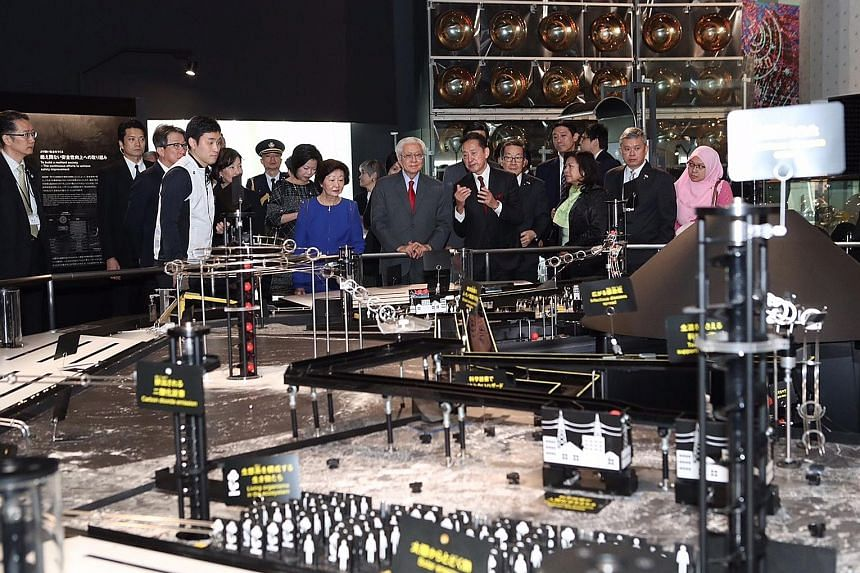 President Tony Tan and his wife Mary viewing Mission Survival: 10 Billion, a physical representation of the hazards facing the planet, including natural and man-made disasters, at Tokyo's National Museum of Emerging Science and Innovation.
