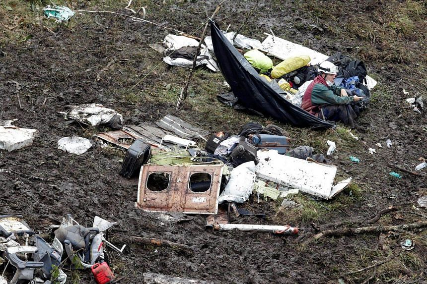 A rescue worker sitting near the wreckage of a plane that crashed into the Colombian jungle with Brazilian soccer team Chapecoense onboard near Medellin, Colombia, on Nov 29, 2016.
