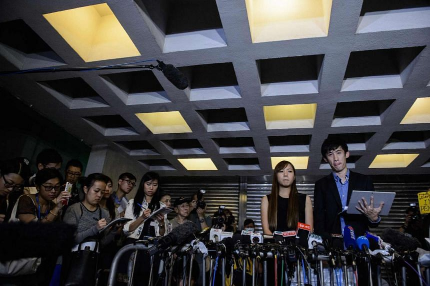 Pro-independence lawmakers Baggio Leung (foreground, right) and Yau Wai-ching (foreground, second right) reacting as they speak to the press outside the High Court in Hong Kong, on Nov 15, 2016.
