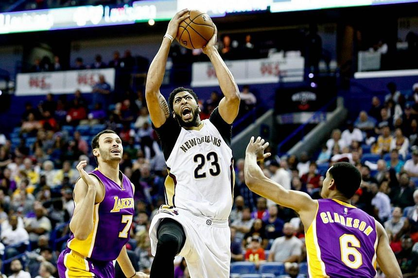 New Orleans Pelicans forward Anthony Davis drives between Los Angeles Lakers forward Larry Nance Jr. and guard Jordan Clarkson during the second half of a game at the Smoothie King Center.