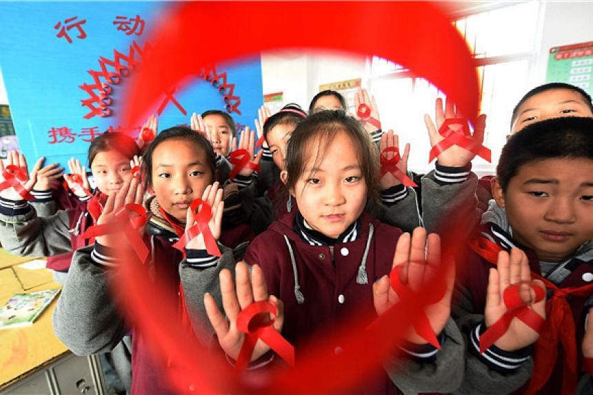 School children holding up red ribbons they made, as part of an HIV/Aids prevention campaign, in Donghai county, Jiangsu province, on Nov 29, 2016.