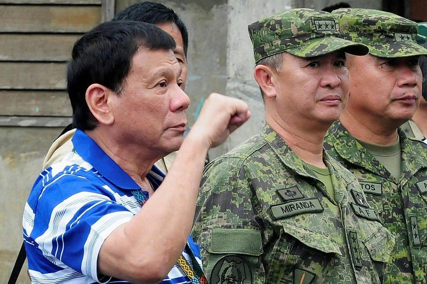 Philippines' President Rodrigo Duterte gestures a clenched fist as he visit soldiers in Butig, Lanao del Sur, southern Philippines on Nov 30, 2016.