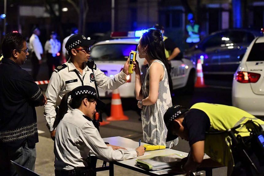 A motorist suspected of drink-driving being tested using a hand-held breath analyser.