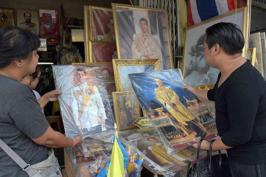 Thai people look at a portrait photo of Crown Prince Maha Vajiralongkorn at a shop along a street in Bangkok on Nov 30, 2016.