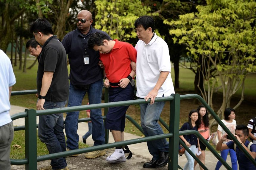 Lee Sze Yong (in red) was brought back to Sembawang Park for police investigations on Jan 1, 2014.