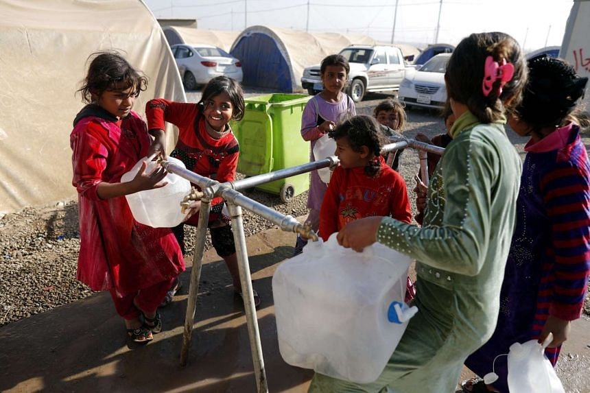 Internally displaced Iraqi children, who fled the ongoing figthing between ISIS and government forces around Mosul, fill a jerrican with water, on Nov 28, 2016, at al-Khazer refugee camp.