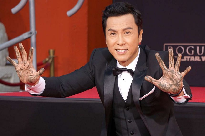 Chinese actor Donnie Yen holds up his cement covered hands during a ceremony honouring him at the TCL Chinese Theatre in Hollywood, California on Nov 30, 2016.