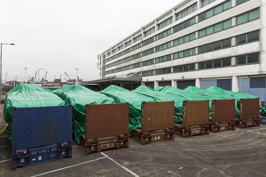 Armored personnel carriers covered with green tarps are parked in a Hong Kong Customs and Excise facility in Tuen Mun on Nov 25, 2016.