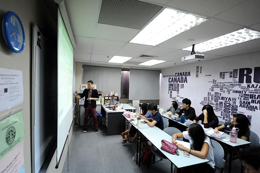 Humanities Hub tutor Chris Ho, 38, conducting an economics class. More students are seeking tuition in subjects that require critical analysis of sources and high-order thinking skills.