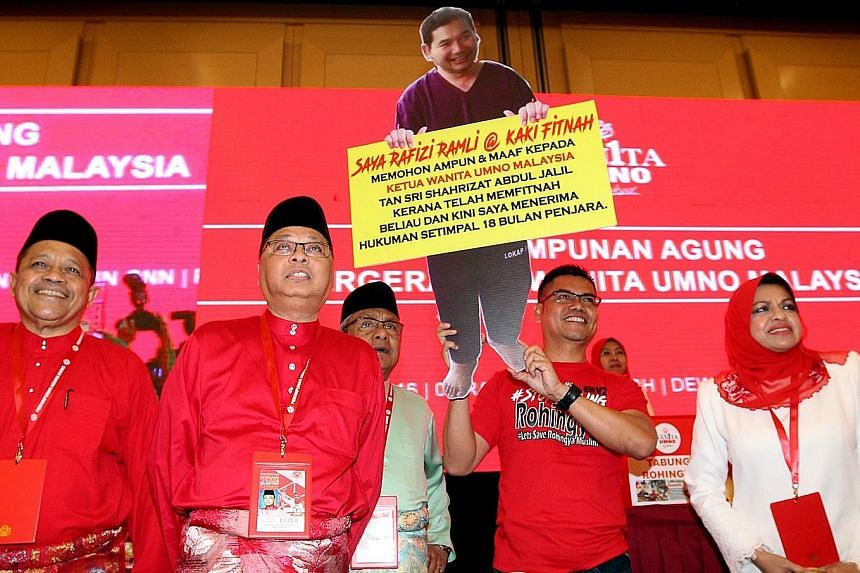 Umno division chief Jamal Yunos holding up a cutout of opposition MP Rafizi Ramli at Umno's annual assembly yesterday, to loud applause from the attending delegates. The poster says that Rafizi is seeking forgiveness from Umno Women chief Shahrizat A