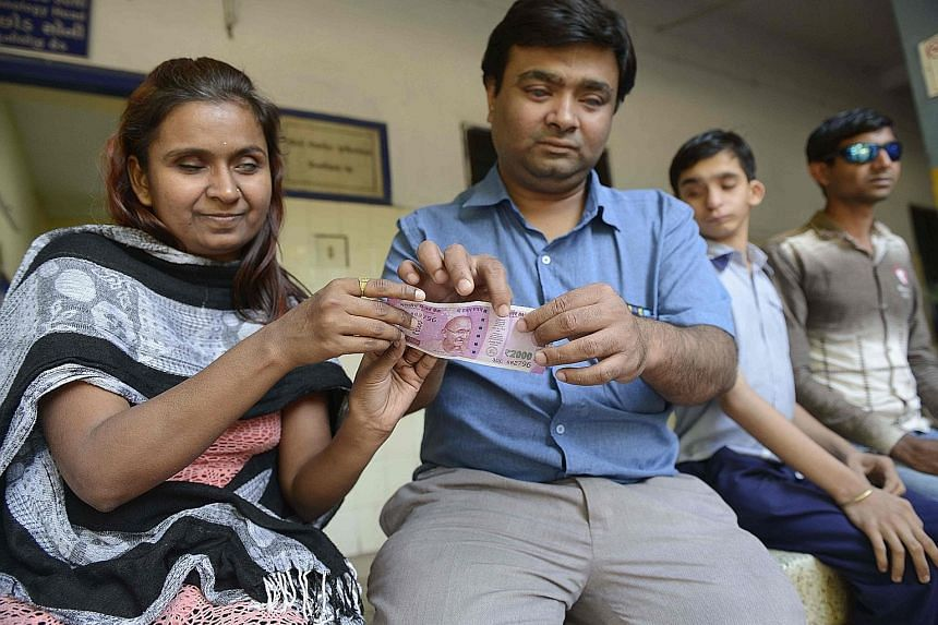 Visually impaired teacher Dilipbhai Chauhan (second from left) on Monday teaching a girl how to identify a new 2,000-rupee note at the Blind People's Association in Ahmedabad. New 500- and 2,000-rupee notes carry improved identification markings for