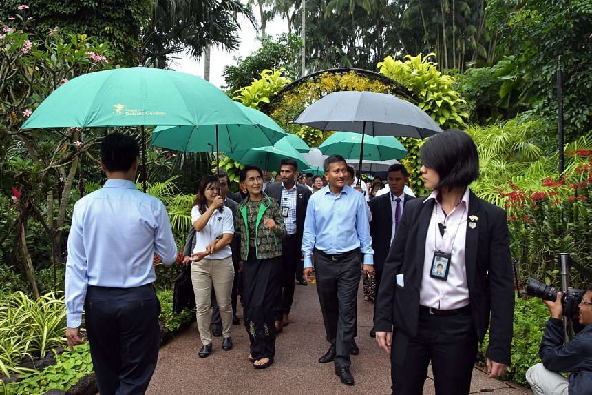 Ms Aung San Suu Kyi is brought on a tour at the National Orchid Garden by Deputy Director of National Orchid Garden Whang Lay Keng (left, beige pants) and Foreign Minister Vivian Balakrishnan, on Dec 1, 2016.