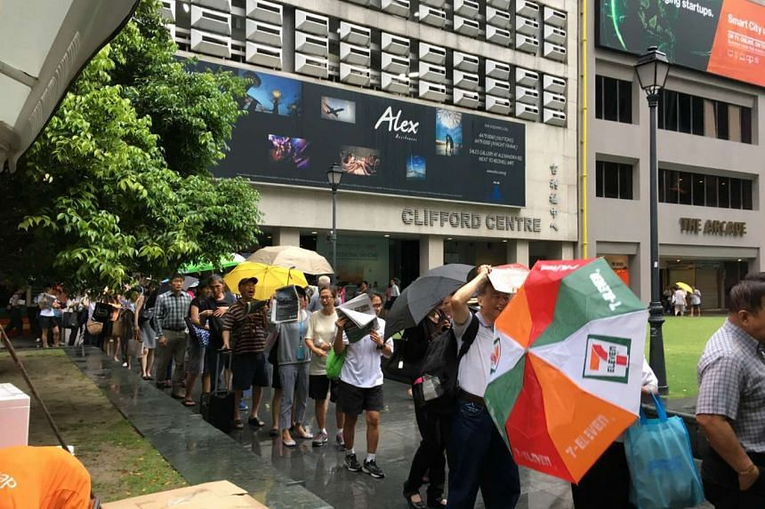 People queue for goodie bags at Raffles Place MRT station on Thursday morning (Dec 1).
