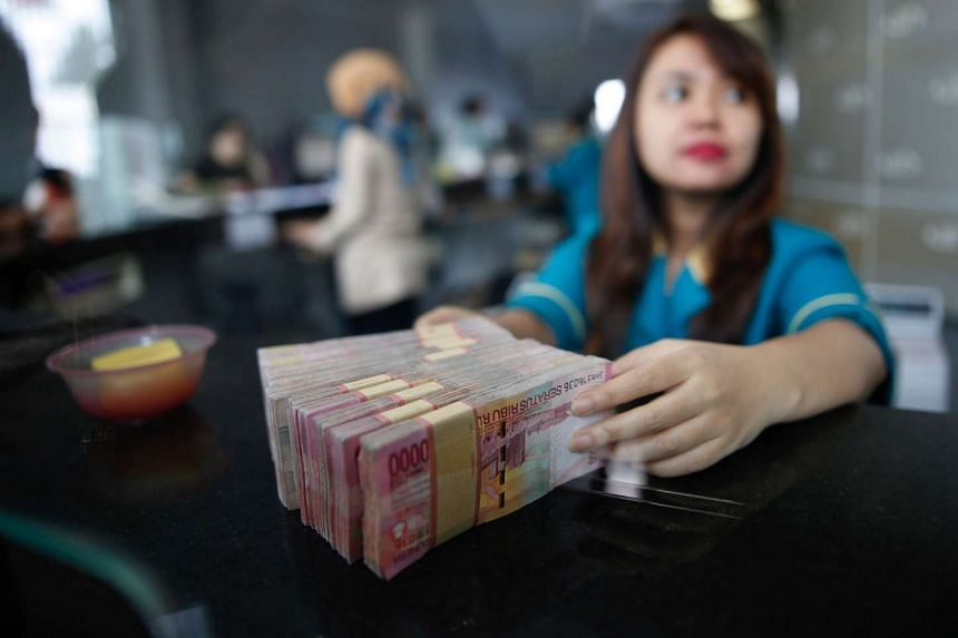 A teller at a money changer handles Indonesia rupiah bank notes in Jakarta.
