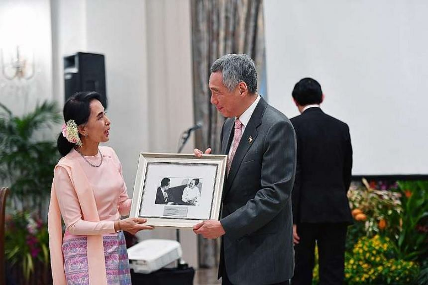 PM Lee Hsien Loong presenting Myanmar State Counsellor Aung San Suu Kyi with a photo of his father, former Prime Minister Lee Kuan Yew, meeting Ms Suu Kyi's mother Khin Kyi in 1965.