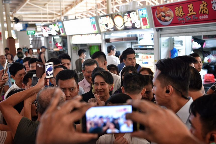 Aung San Suu Kyi gets mobbed by the crowd as she leaves Ghim Moh Market.