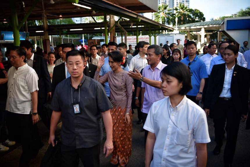 Aung San Suu Kyi waves to patrons at the Ghim Moh Market on Dec 2, 2016.